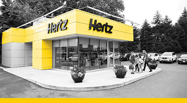 Grey scale image of a yellow Hertz building.