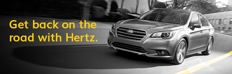 Get back on the road with hertz text with a grey background image of a Subaru driving on the road.