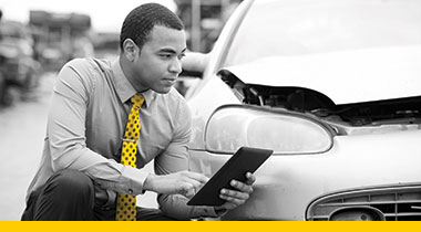 Grey scale image of a man kneeling in a yellow tie with an iPad beside a vehicle that is damaged.