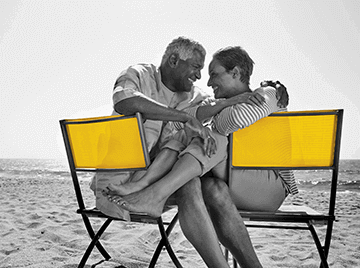 A senior citizen male and female couple sit on yellow chairs and smile at each other while spending time at the beach.