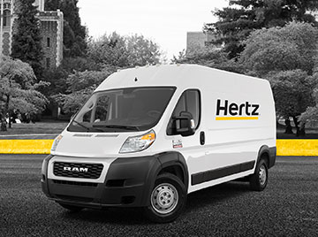 White cargo van with Hertz logo on side and yellow line with trees in the background.