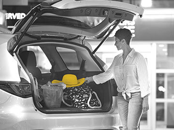 Black and white photo of woman pulling a yellow hat out of the trunk of her SUV.