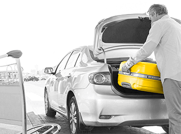 Black and white image of man pulling a yellow suitcase out of the trunk of his car.