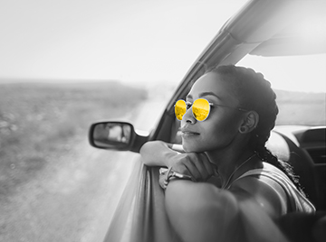 Black and white image of young woman leaning outside the car window wearing yellow sunglasses.