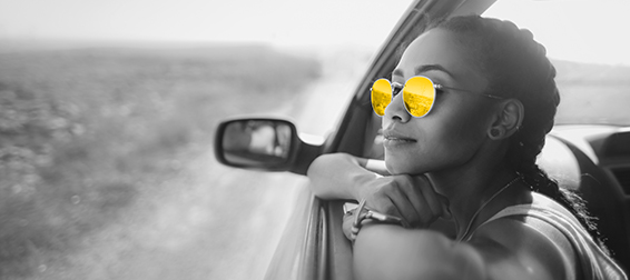 A woman in her 20s wearing round sunglasses rests her chin on her hands as she looks out of a car driver's side window.