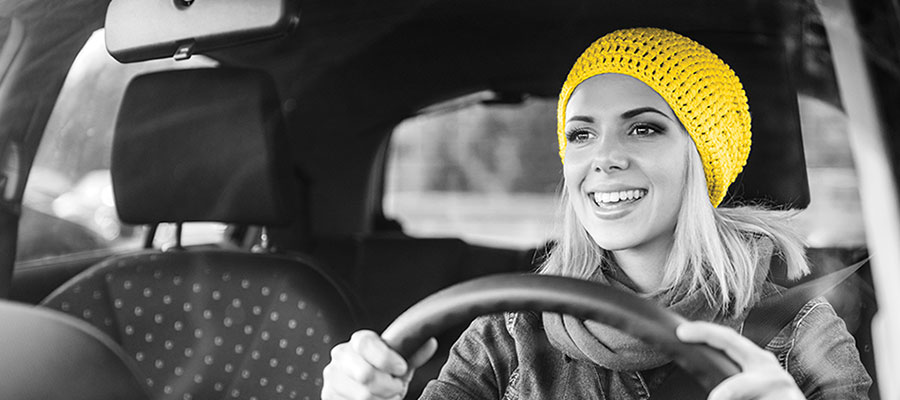 A woman in her early 20s wears a yellow beanie and smiles as she sits in the driver's seat of a rental car.