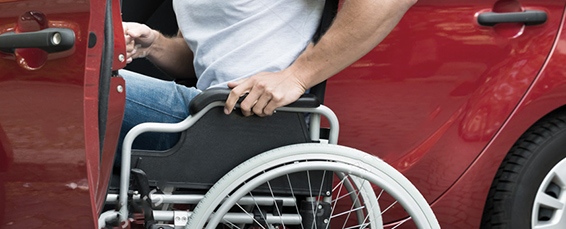 A man wearing a light gray shirt and blue jeans prepares to push himself out of his wheelchair and into a red car.